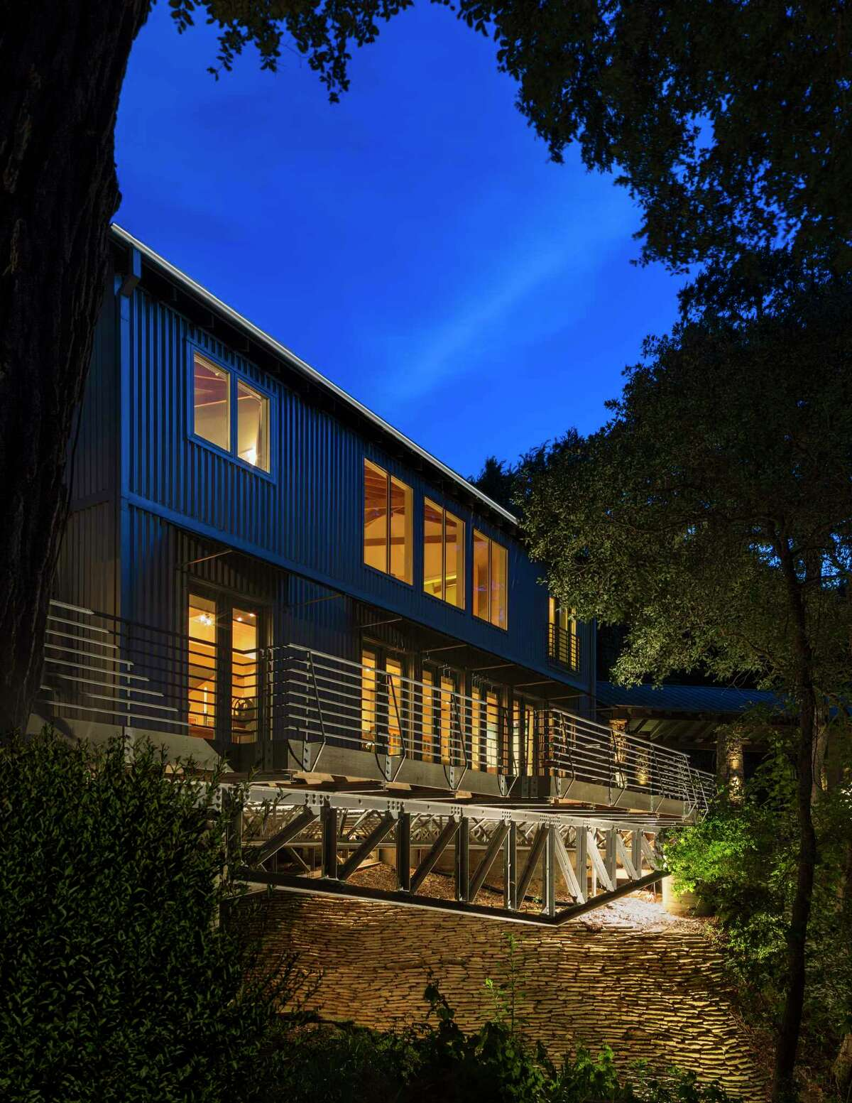 Lights illuminate the architectural structure of the home's base.