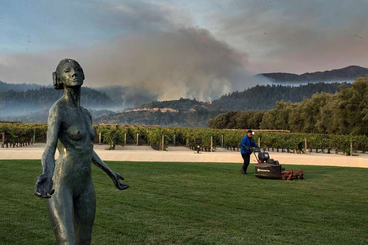 Statue at the Mondavi Winery and a groundsman mows lawn as fires burn on Monday, Oct. 16, 2017 in Oakville, CA.