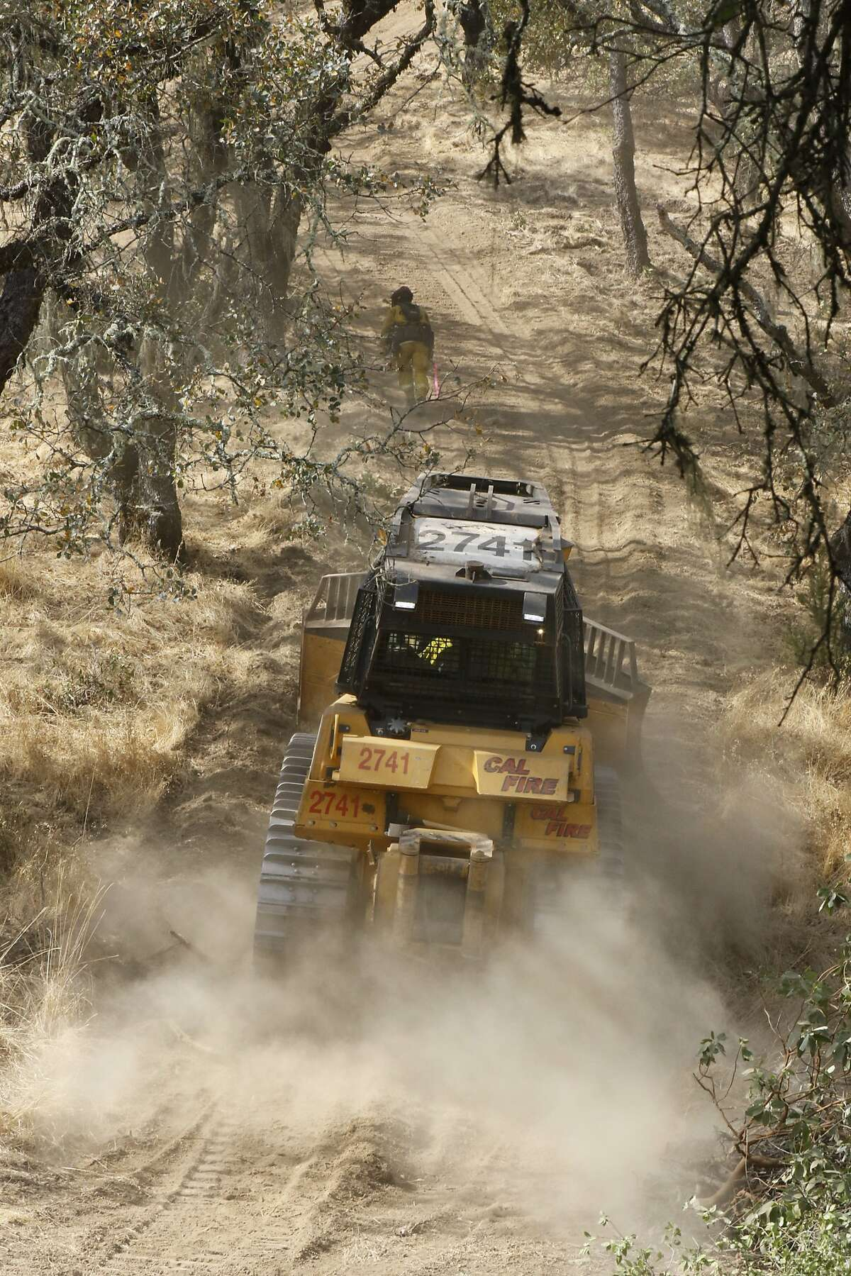 Firefighter and a bulldozer head to the fire line on Monday, Oct. 16, 2017 in Oakville, CA.