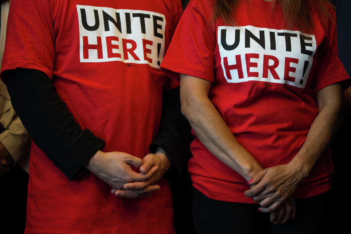 Members from Unite Here!, a labor union, stand with hands clasped as Mayor Tim Burgess announces a community benefits package as a part of the Washington State Convention Center renovation, at Seattle City Hall on Monday, Oct. 16 2017.