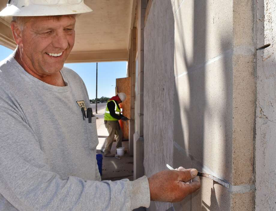 Andy West, foreman for Mid-Continental Restoration, applies mortar between stones at the Conrad Lofts project in downtown Plainview. He uses a special jointer to bring the façade of the old Plainview Hilton Hotel back to repair. West expects his company to be at work through Christmas replacing mortar, brick and broken stone.