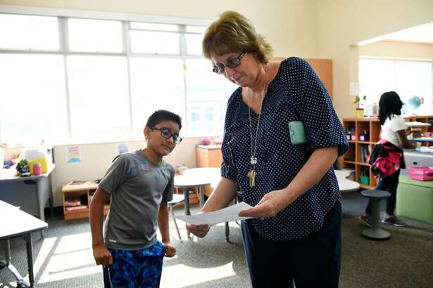 Principal Teresa Ruffoni, who lost her home in Santa Rosa to recent wild fires, looks some work by 4th grade student Andres Garcia, as she checks in on classrooms at Richard Crane Elementary School in Santa Rosa, Calif, on Monday October 16, 2017.