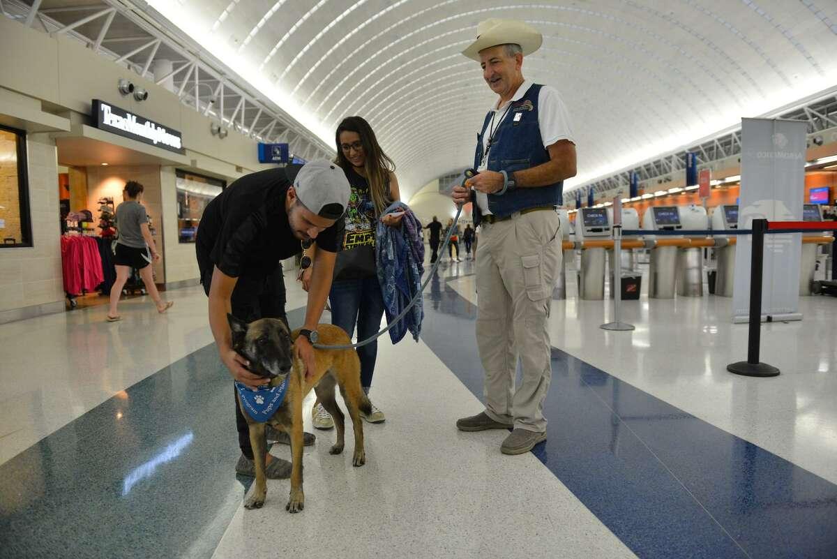 Ricardo Faudoa and Ana Ramirez greet Airport Ambassador Benjamin Bott and his Pups and Planes dog, Helo, recently at the San Antonio International Airport.