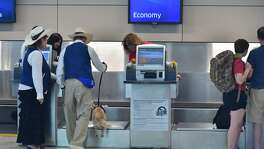 Airport Ambassadors Claudia and Jason Fisch of the Pups and Planes program let their dog greet United Airline employee recently at the San Antonio International Airport. A reader agrees with an E-N editorial, which stated that the airport is not holding the city back economically.