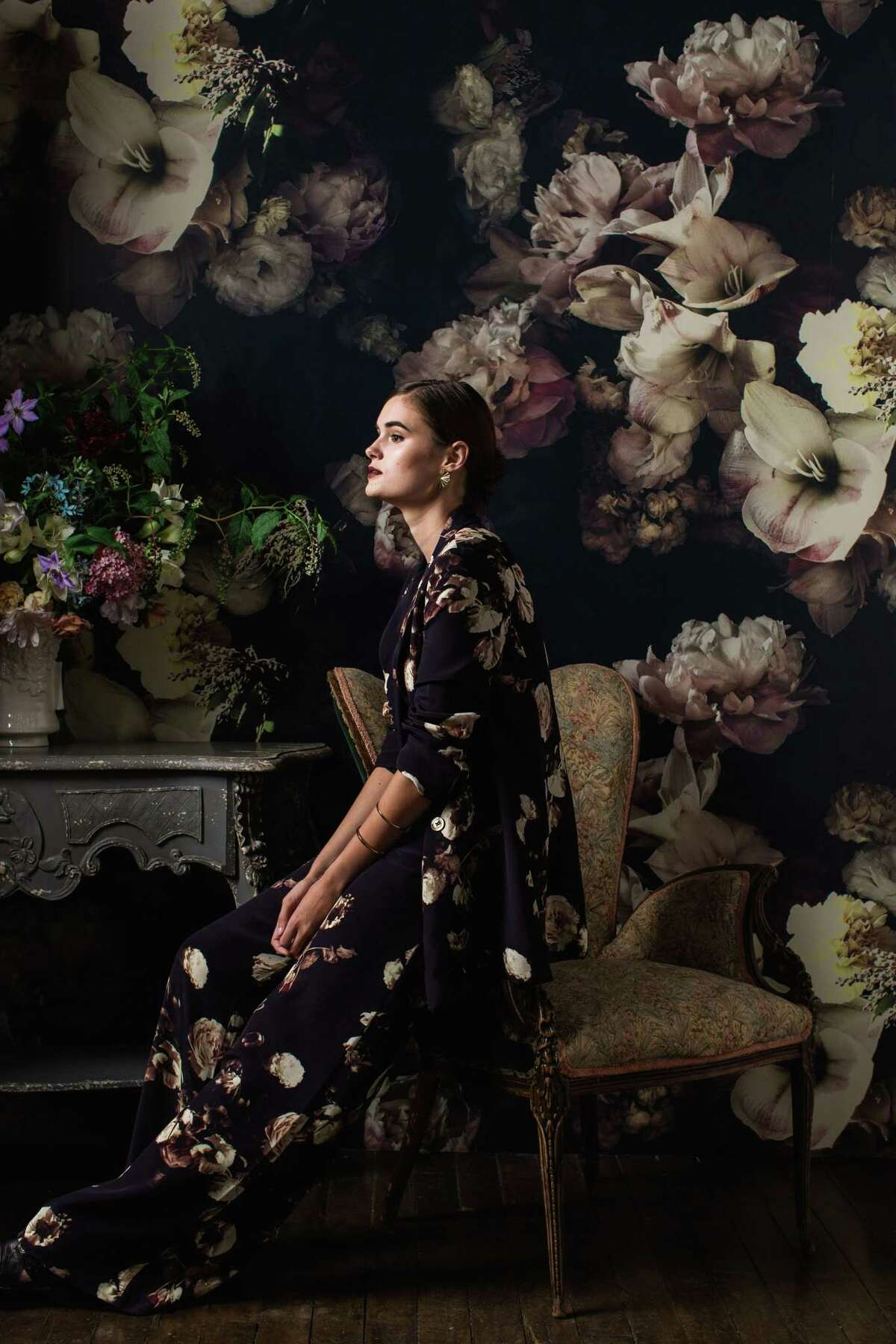 A model wears clothing from Ashley Woodson Bailey's Dutch Love collection with wallpaper by Bailey as a backdrop.