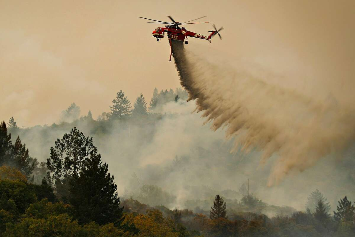 A Cal Fire helicopter drops water on a smoldering area as the Partrick Fire continue to burn slowly east of Sonoma, Calif., on Thursday, October 12, 2017.