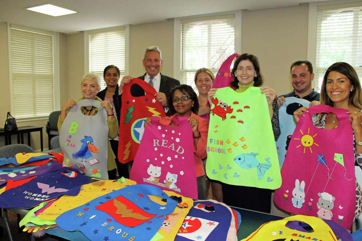 Family Centers and UBS Financial Services Inc. employees display the hand-made capes that will be distributed to pre-school students who meet their reading goals. From left to right, Arleme Tahmin, branch service associate for UBS; Yenny Toone, Family Centers director of early childhood education; Edward Emanuel, UBS' director and branch manager; Andrea Anderson, client services assistant; Carter Ashforth, Family Centers development coordinator; Rena Howard, client service associate; Chris Angotto, the preschool's head administrative teacher; and Diana Neufuss, executive team assistance, show off the capes.