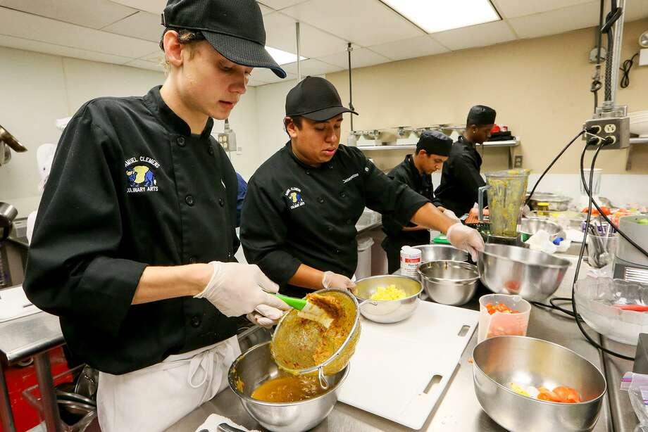 Culinary arts students James Rowe (from left), 17, and Cameron Patino, 18, from Clemens, work beside Steele's Jose Aponte, 19, and Damon Rush, 17, in the 2017 St. Philip's College Best Tasting Salsa Scholarship Competition, at the school on Oct. 11. Other high school teams competing were  La Vernia, Taft, Whitehouse, Floresville,  Brandeis and East Central. Photo: Marvin Pfeiffer /San Antonio Express-News / Express-News 2017