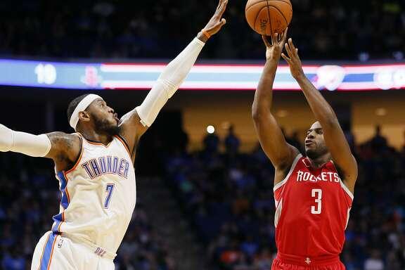 Houston Rockets guard Chris Paul (3) shoots as Oklahoma City Thunder forward Carmelo Anthony (7) defends during the first quarter of an NBA preseason basketball game in Tulsa, Okla., Tuesday, Oct. 3, 2017. (AP Photo/Sue Ogrocki)