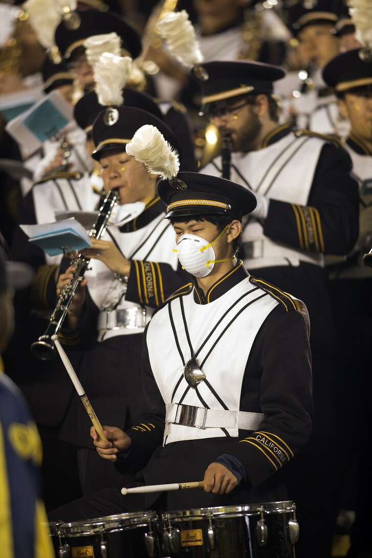 A member of the California marching band wears a dust mask during the first quarter of California's NCAA college football game against Washington State, Friday, Oct. 13, 2017, in Berkeley, Calif. Wildfires in the North Bay have resulted in poor air quality. (AP Photo/D. Ross Cameron)