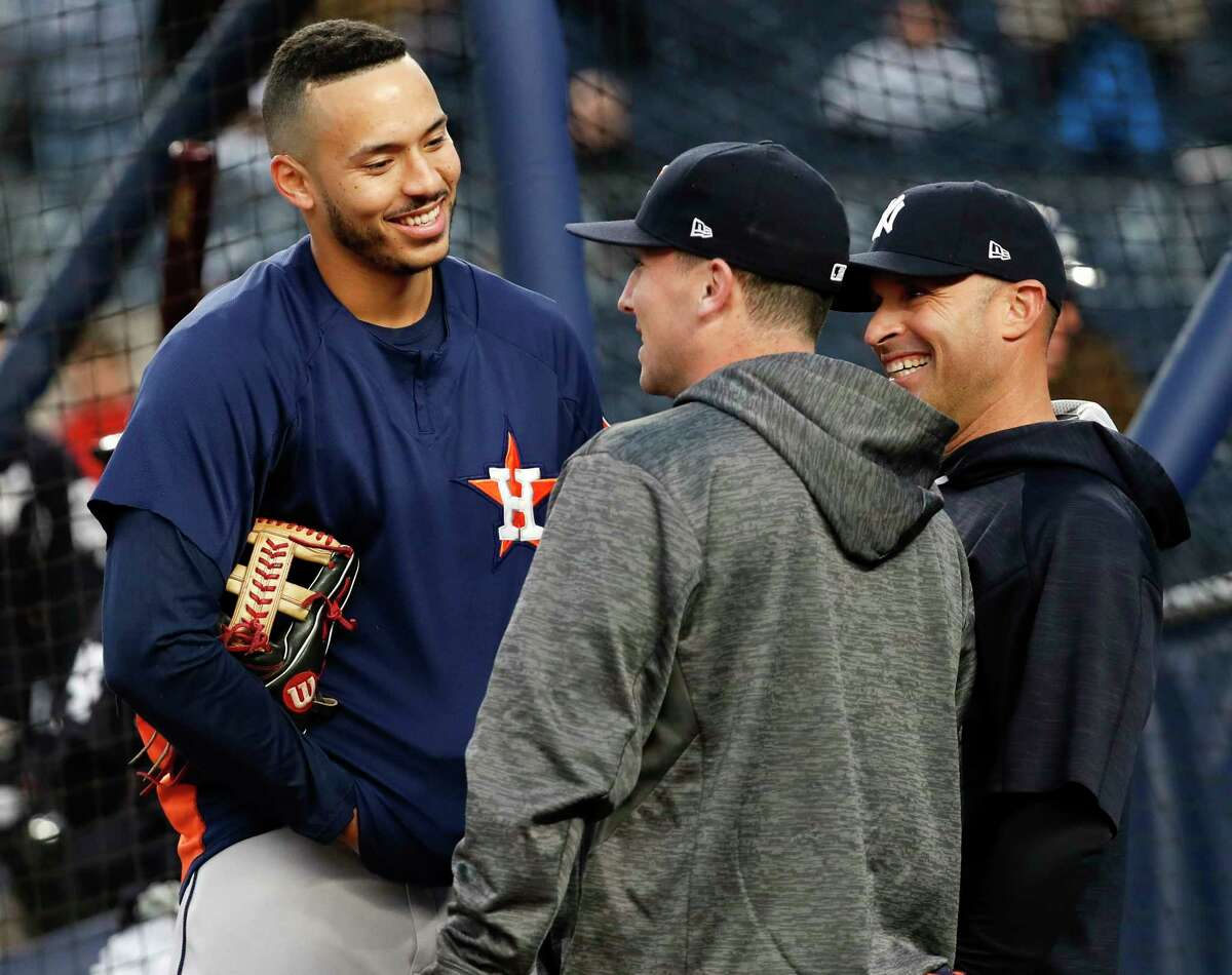 Houston Astros shortstop Carlos Correa (1) and third baseman Alex Bregman (2) talk to New York Yankees third base coach Joe Espada before Game 3 of the ALCS at Yankee Stadium on Monday, Oct. 16, 2017, in New York.