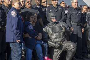 """Isabella Gambo, her brother Josiah and Batman, Ft. Worth Officer Damon Cole, pose with their new """"brothers in blue"""" after Midland Police Deputy Chief Jeff Darr swore them in as honorary officers 10/16/17 during a fundraiser at Monterrey Restaurant to help pay for her medical expenses. Tim Fischer/Reporter-Telegram"""