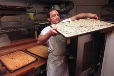 FOCACCIA15.2/C/02MAR95/FD/Michael Maloney Chris Miller of L'Osteria Del Forno in the North Beach area lifts a focaccia tray from the oven top to the oven. Behind him are freshly baked focaccia.