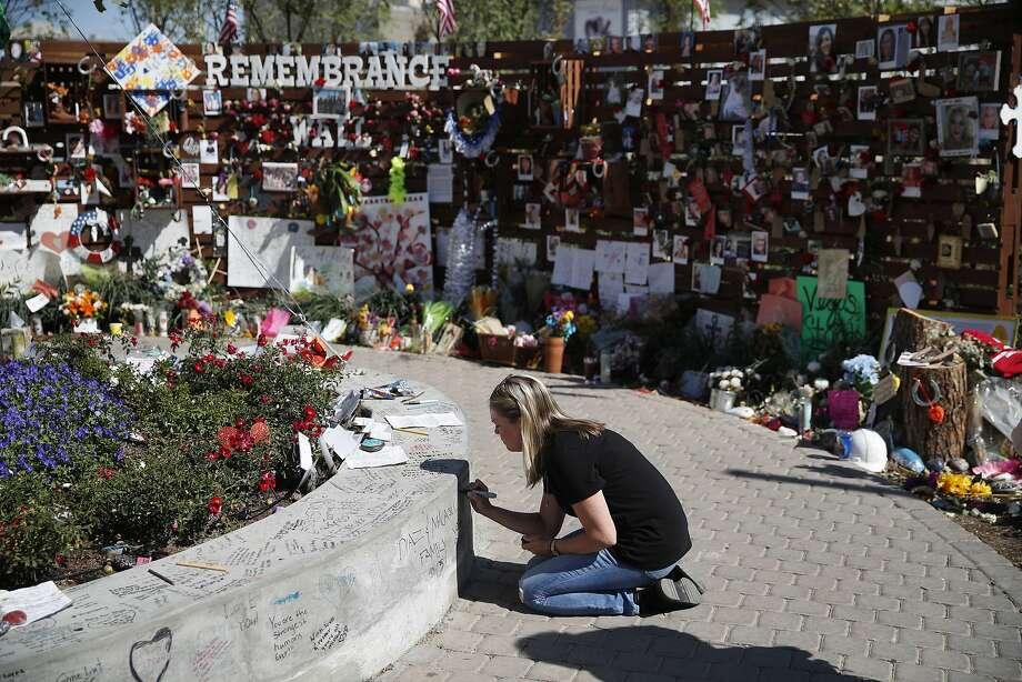 Jenni Tillett writes a message at the Las Vegas Community Healing Garden, Monday, Oct. 16, 2017, in Las Vegas. The garden was built as a memorial for the victims of the recent mass shooting in Las Vegas. (AP Photo/John Locher) Photo: John Locher, Associated Press