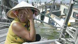 A distraught Le An Thi holds back tears while overlooking her family's  shrimping boat as it rests in the water after sinking at the dock as Rockport tries to recover from Hurricane Harvey devastation on September 26, 2017.  The family of the owner, all Vietnamese immigrants, had just invested $75,000 three days prior to seeing it destroyed.