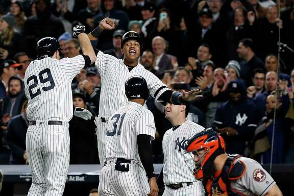New York Yankees third baseman Todd Frazier (29) and second baseman Starlin Castro and center fielder Aaron Hicks (31) celebrate Frazier's 3-run home run off Houston Astros starting pitcher Charlie Morton during the second inning of Game 3 of the ALCS at Yankee Stadium on Monday, Oct. 16, 2017, in New York.