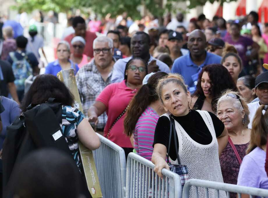 Thousands wait to apply for food assistance at the George R. Brown Convention Center on Oct. 6. More than 932,00 Harris County residents have received help. Photo: Jon Shapley, Staff Photographer / Houston Chronicle
