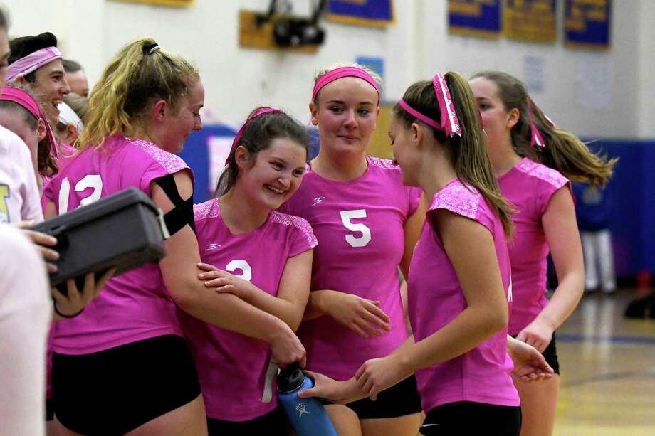 Newtown volleyball players, from left, Erin Mitchell (12), Mollie Goudy (3), Julia Anderson (5), Rachel O'Grady, and Zoe Beals celebrate their win at the conclusion of the girls volleyball match between Newtown and Pomperaug high schools, October 16, 2017, at Newtown High School. Photo: Krista Benson / 00089652A