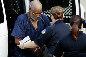 FILE- In this July 24, 2017, file photo, James Matthew Bradley Jr., left, arrives at the federal courthouse for a hearing in San Antonio. Bradley, the driver of a semitrailer packed with almost three dozen immigrants, pleaded guilty on Monday, Oc. 16, to making the deadly smuggling run. He faces up to life imprisonment. (AP Photo/Eric Gay, File)
