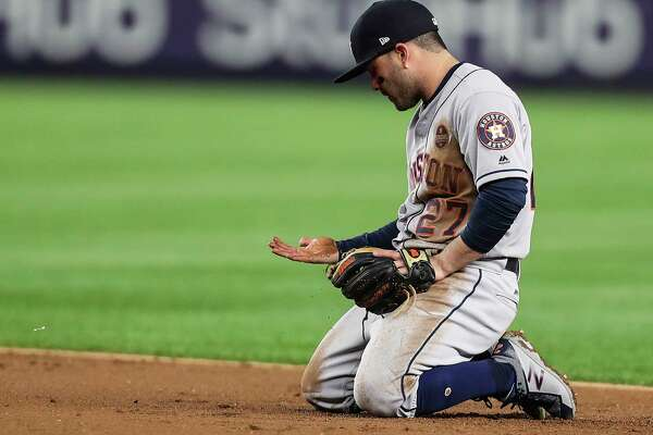 Houston Astros second baseman Jose Altuve looks down at his hand after making a diving stop and throwing out New York Yankees shortstop Didi Gregorius at first during the third inning of Game 3 of the ALCS at Yankee Stadium on Monday, Oct. 16, 2017, in New York.