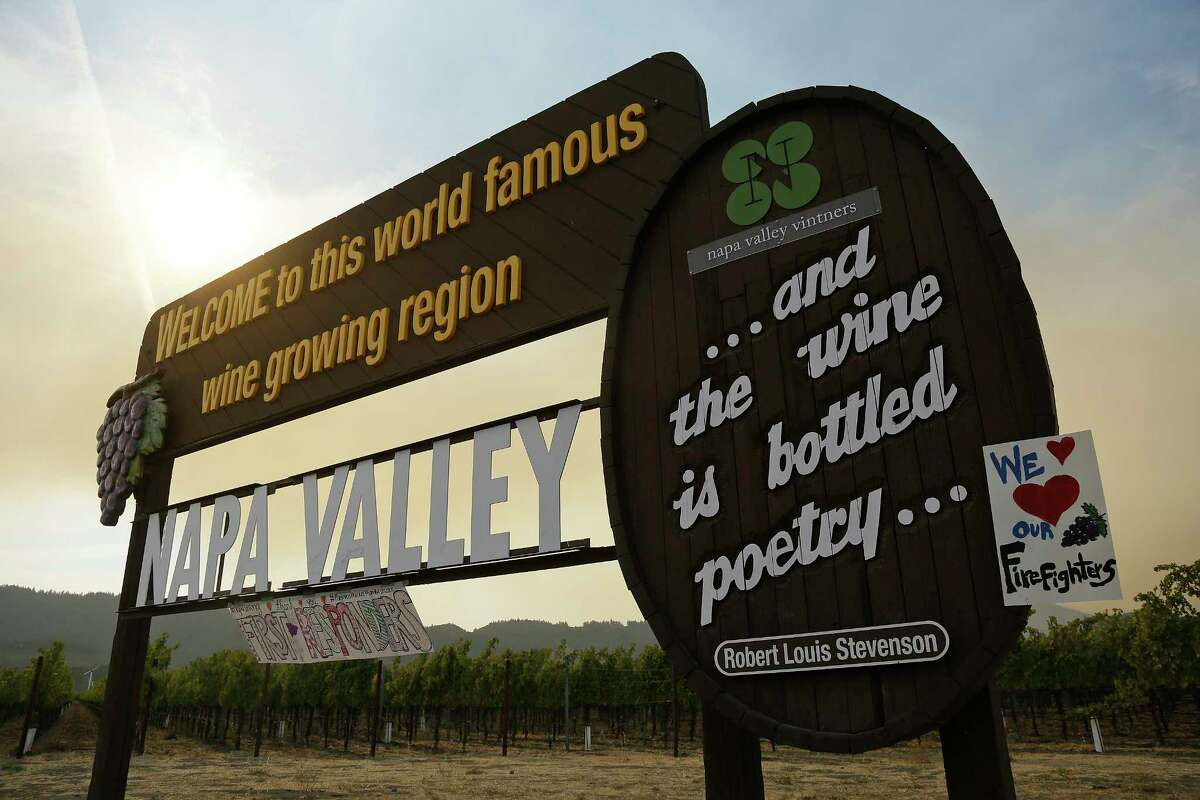 Smoke from the Nuns fire wafts over the Welcome to the Napa Valley sign, Monday, Oct. 16, 2017, in Oakville, Calif. State and local officials say they are trying to get people back into their homes, but they cautioned that it could take days and even weeks for neighborhoods hard hit by Northern California wildfires.