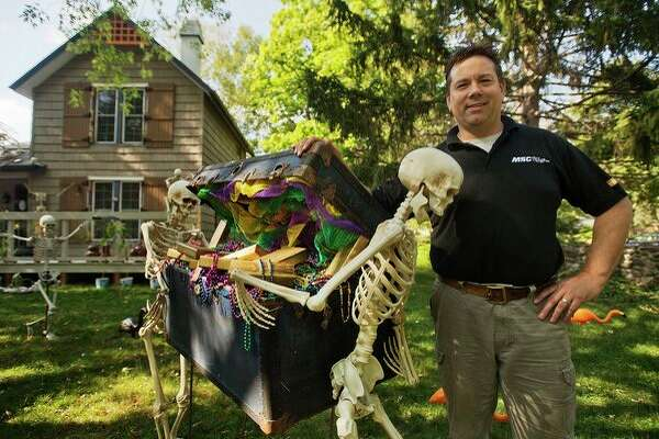 Rich Marshall poses for a photo among the elaborate Halloween-themed displays on his front lawn on Ashman Street. Rich is responsible for the decorations on the outside of their home, while his wife, Karen, has decorated the interior for the Halloween season. (Katy Kildee/kkildee@mdn.net)