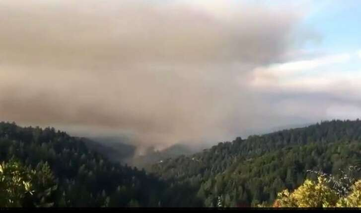 At least 250 firefighters were battling a new wildfire Tuesday morning in the Santa Cruz Mountains near Boulder Creek that has burned at least four houses and injured five firefighter, including an inmate firefighter.