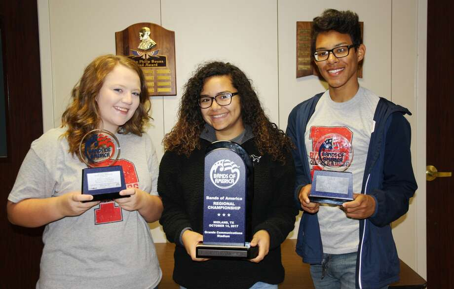 Plainview High School color guard captains Sawyer Tirey (left), Trini Perez and Eliah Ybarra pose with three of the five trophies the PHS Powerhouse of the Plains Band received in the Bands of America competition in Midland on Oct. 14.