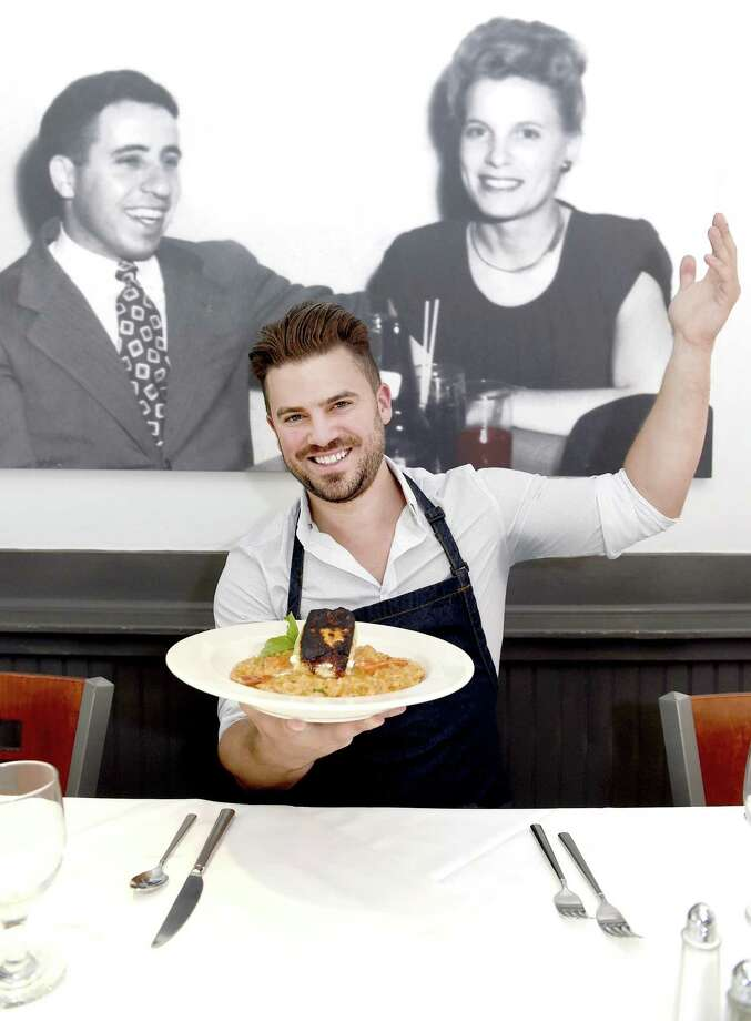 Owner and Chef Ryan Durant , with a photo featuring his inspirational grand parents, in his Assagio restaurant in Branford with the restaurant's risotto with blackened Chilean sea bass and picked lobster meat. Ingredients include Chilean sea bass, lobster meat, arborio rice, shallots, cream, butter, parmigiana cheese, red sauce, basil, and seafood stock, (for substitute can use : clam juice). Photo: Peter Hvizdak / Hearst Connecticut Media / New Haven Register