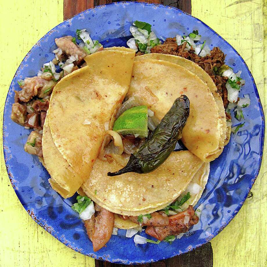 Clockwise from top left: Lengua, asada and tripas tacos on corn tortillas with onions, cilantro, lime, grilled onions and a roasted jalapeño from Tacos El Mexicano. Photo: Mike Sutter /San Antonio Express-News