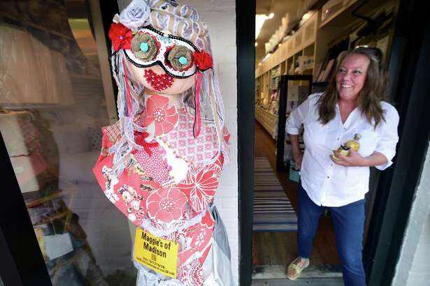 Jan Nelson takes a look at Persephone, Goddess of Spring, Queen of the Underworld, outside of Maggie's of Madison Monday. This is one entry in the Madison Chamber of Commerce's 8th annual Sea, Shop, Scare! event.