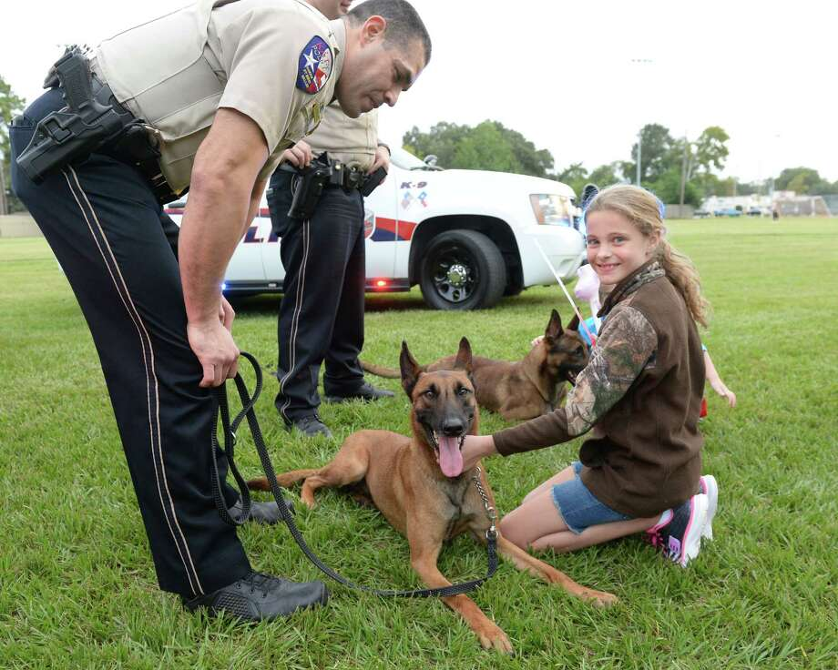 Madyson Fleener, 9, visits with Katy K-9 Officer Luna as handler Officer Rodriguez looks on during the National Night Out festivities at Katy City Park on Oct. 10. Photo: Craig Moseley, Staff / ©2017 Houston Chronicle