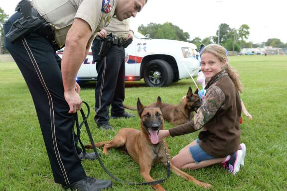 Madyson Fleener, 9, visits with Katy K-9 Officer Luna as handler Officer Rodriguez looks on during the National Night Out festivities at Katy City Park on Oct. 10.