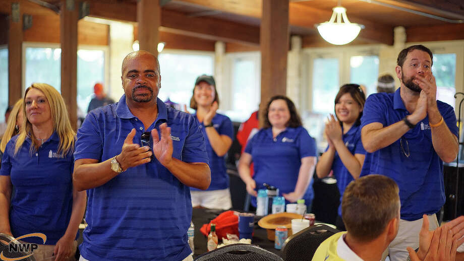 Employees of The Lighthouse of Houston applaud as the donation amount is announced from the Northwest Petroleum's second annual Charity Classic Golf Tournament. Photo: Courtesy Photo