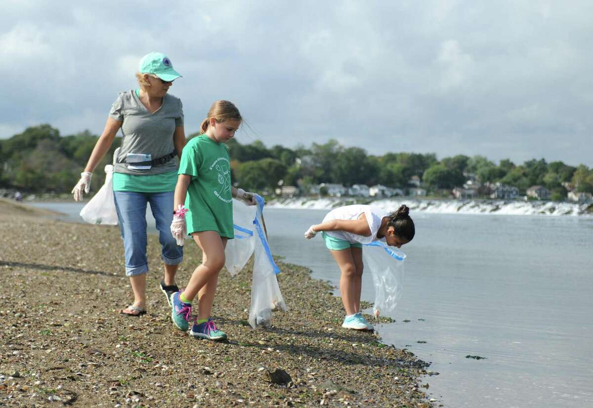 Stamford residents Barbara Cassidy, left, Sara Caldarone, center, 9, and Sarah Takarout, 9, pick up trash from the beach during the SoundWaters Coastal Cleanup at Cove Island Park in Stamford, Conn. Sunday, Oct. 15, 2017. SoundWaters distributed golves and bags to any beachgoers wishing to lend a hand to clean up trash and debris from the beach.