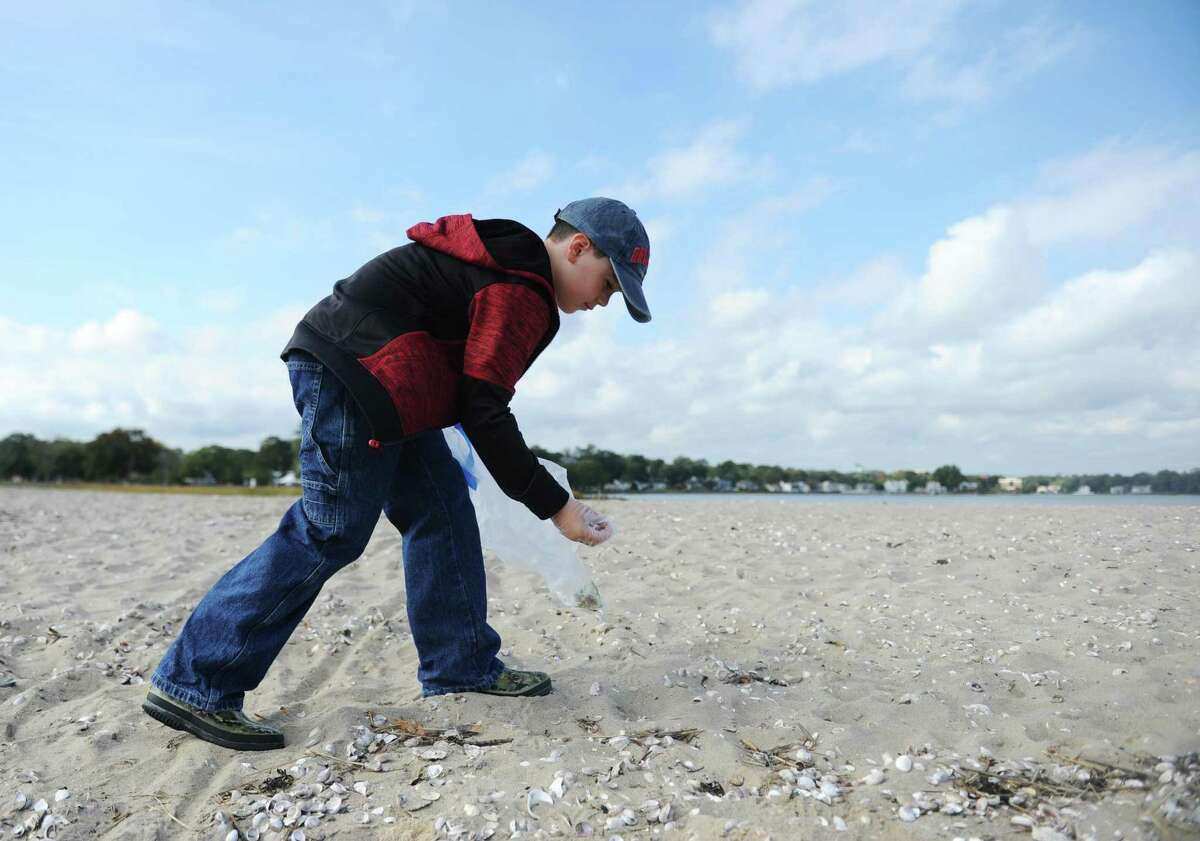 Samuel Wolff, 8, of Stamford, picks up a cigarette butt off the beach during the SoundWaters Coastal Cleanup at Cove Island Park in Stamford, Conn. Sunday, Oct. 15, 2017. SoundWaters distributed golves and bags to any beachgoers wishing to lend a hand to clean up trash and debris from the beach.