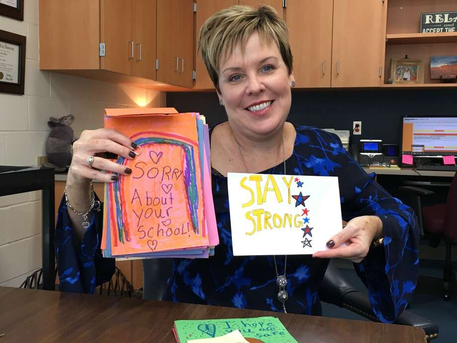 Moore Elementary has received cards, support and donations from around the country including North Carolina, Utah, Montana and Idaho. Principal Patricia Myers displays some of the cards received. Along with other duties, two secretaries are kept busy writing thank-yous to those assisting the school. Photo: Karen Zurawski