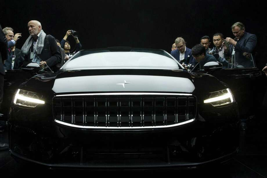 Attendees look at the Polestar 1 during its unveiling in Shanghai, China Tuesday. Volvo Cars' performance electric car brand, Polestar, unveiled a four-seat coupe in lightweight carbon fiber as its first model Tuesday, adding to competition in a market dominated until now by Tesla. Photo: Chinatopix / Chinatopix