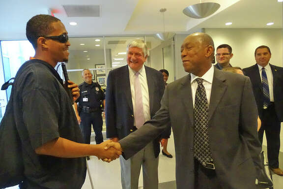 Houston Mayor Sylvester Turner meets with Lighthouse client Mikey Fields, as Lighthouse President Gibson DuTerroil looks on.