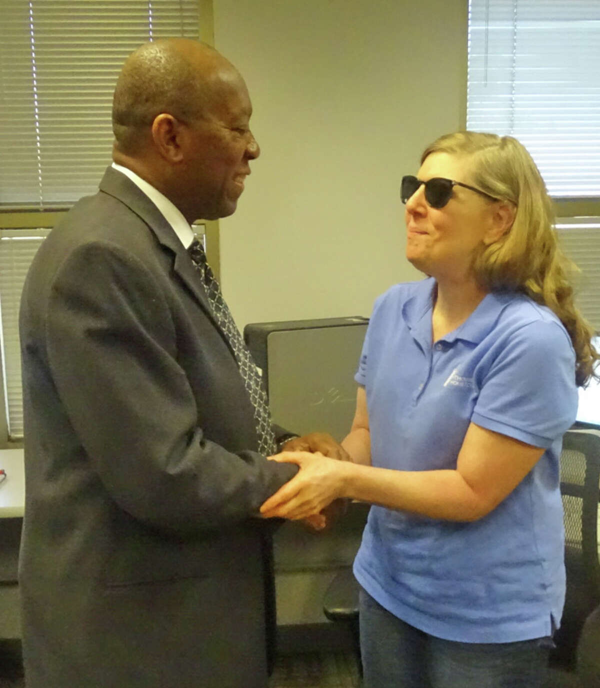 HoustonMayor Sylvester Turner visits with Lisa Carpenter, who works as a medical transcriptionist at The Lighthouse of Houston.