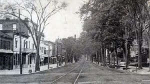 Postcard of Broad Street (Broadway) in Schuylerville looking south from Ferry Street from between 1907 and 1912 with no cars or carriages shown. The Bullard block and trolley lines can be seen as well as the chimney of the Bullard Paper Mill in the distance.