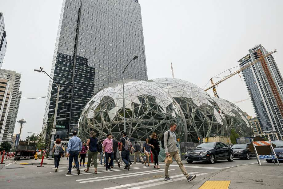 Pedestrians walk past a recently built trio of geodesic domes that are part of the Seattle headquarters for Amazon, Sept. 7, 2017. The online retail giant said it was searching for a second headquarters in North America in 2017, a huge new development that would cost as much as $5 billion to build and run, and house as many as 50,000 employees. (Stuart Isett/The New York Times) Photo: STUART ISETT, NYT