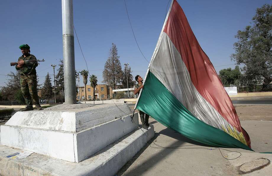 An Iraqi forces member takes down a Kurdish flag as government troops took control of Kirkuk. Photo: AHMAD AL-RUBAYE, AFP/Getty Images