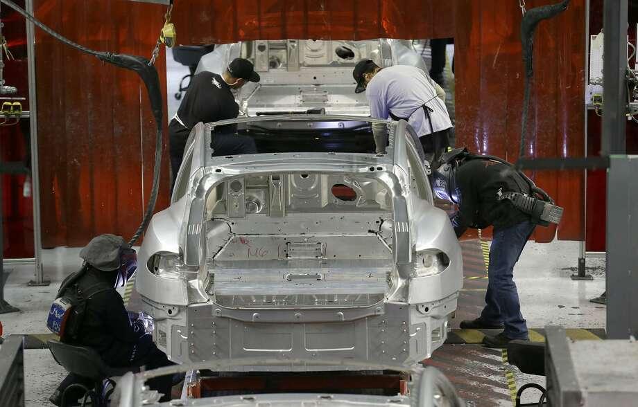 Tesla employees work on a Model S cars in the Tesla factory in Fremont, Calif., Thursday, May 14, 2015. (AP Photo/Jeff Chiu) Photo: Jeff Chiu/AP