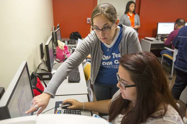 Elizabeth Severance, center, college advisor at Somerset High School, guides Rosalinda Escobar, a senior at Stevens High School, through the application process for financial aid during a Student Aid Saturday in March 2013. All graduating seniors should fill out the form.