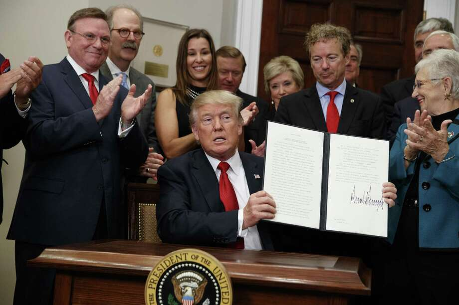 President Donald Trump shows an executive order on health care that he signed Thursday in the Roosevelt Room of the White House. His orders will have the effect of giving healthy consumers bare-bones plans, herding the ill into plans what will end up costing more. Photo: Evan Vucci /Associated Press / Copyright 2017 The Associated Press. All rights reserved.