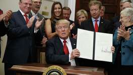 President Donald Trump shows an executive order on health care that he signed Thursday in the Roosevelt Room of the White House. His orders will have the effect of giving healthy consumers bare-bones plans, herding the ill into plans what will end up costing more.