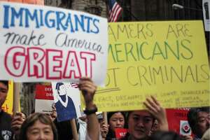 Protesters hold up signs during a demonstration against President Donald Trump during a rally in support of the Deferred Action for Childhood Arrivals (DACA), also known as Dream Act, near the Trump Tower in New York on October 5. Trump has made restrictionist demands in exchange for his support of new Dreamer legislation.