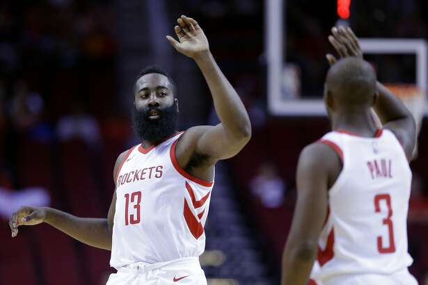 Houston Rockets guard James Harden (13) and Chris Paul (3 )high five in the first half of an NBA exhibition basketball game against the Shanghai Sharks Thursday, Oct. 5, 2017, in Houston. (AP Photo/Michael Wyke)