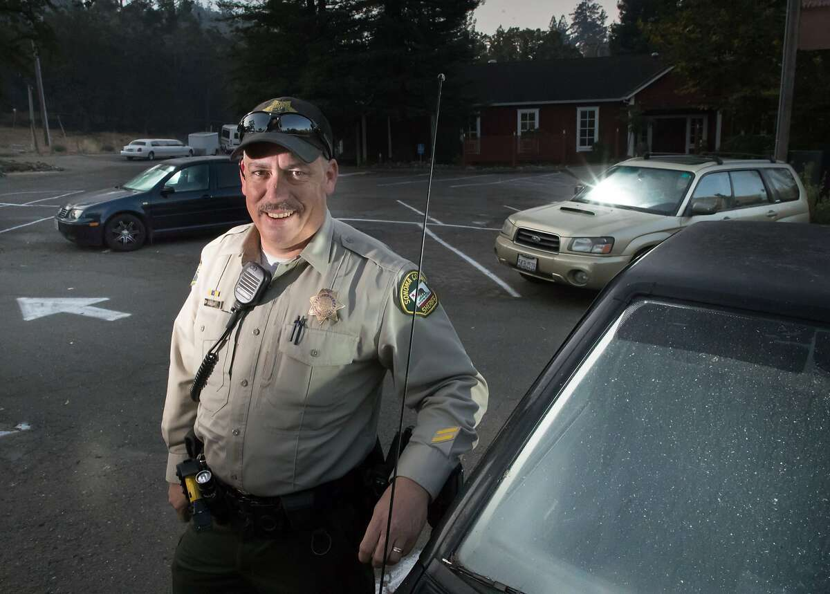 Deputy Mark Aldridge with some of the actual cars at Mark West Springs parking lot where he saved 35 people from the fire, Tuesday, Oct. 17, 2017 in Santa Rosa, CA.